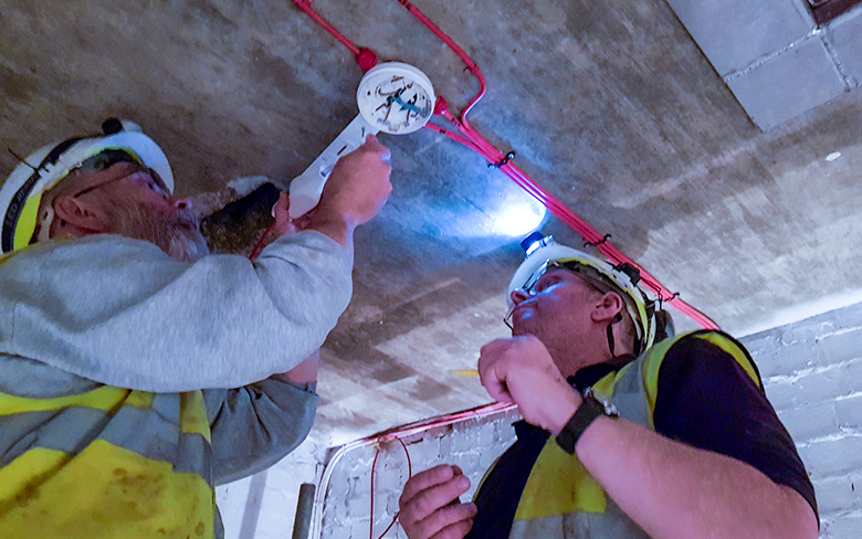 Two men installing Scorpion device to a detector in a lift shaft